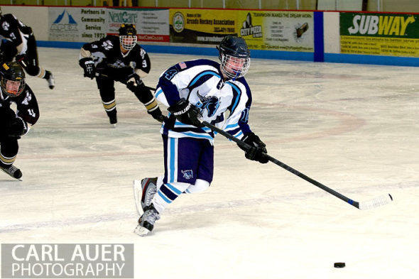 January 11th, 2013: A Ralston Valley hockey player brings the puck down the ice with the Battle Mountain High School team in pursuit in their game at the Apex Ice Arena on Friday night in Arvada, CO