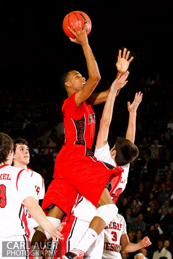 An Eaglecrest player elevates over the Regis Jesuit defense for a shot attempt in their CHSAA 5A Great 8 game at the Denver Coliseum on Friday night
