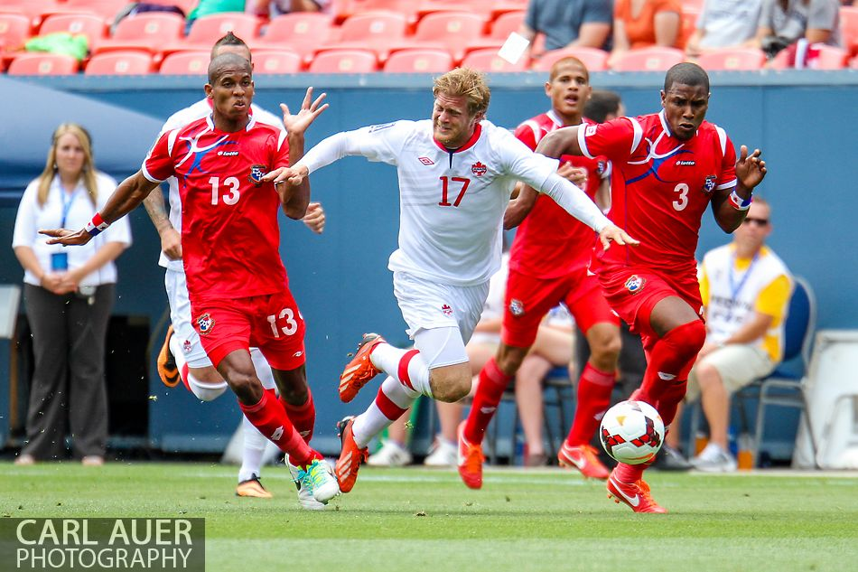 July 14 2013:  Canada Defender Marcel De Jong (17) gets tripped up as he attempts to dribble the ball between Panama Defender Jean Carlos Cedeño (13) and Defender Harold Cummings (3) during first half action of the CONCACAF Gold Cup soccer match between Panama and Canada at Sports Authority Field in Denver, CO. USA.