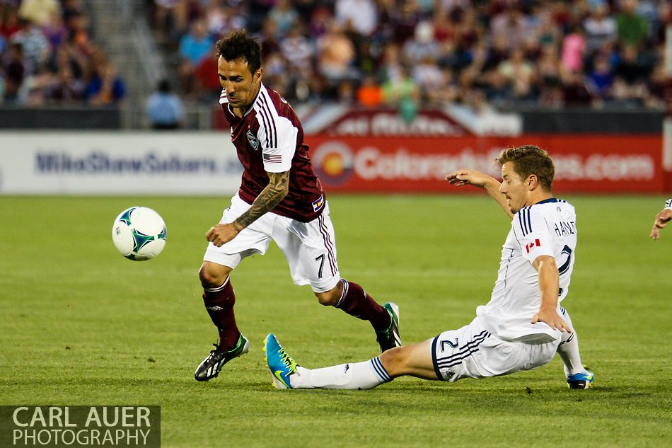 August 17th, 2013 - Colorado Rapids forward Vicente Sánchez (7) attempts to avoid a tackle by Vancouver Whitecaps FC defender Jordan Harvey (2) in the first half of the Major League Soccer match between the Vancouver Whitecaps FC and the Colorado Rapids at Dick's Sporting Goods Park in Commerce City, CO